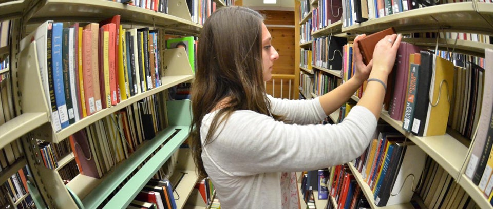 Girl searching through the library stacks