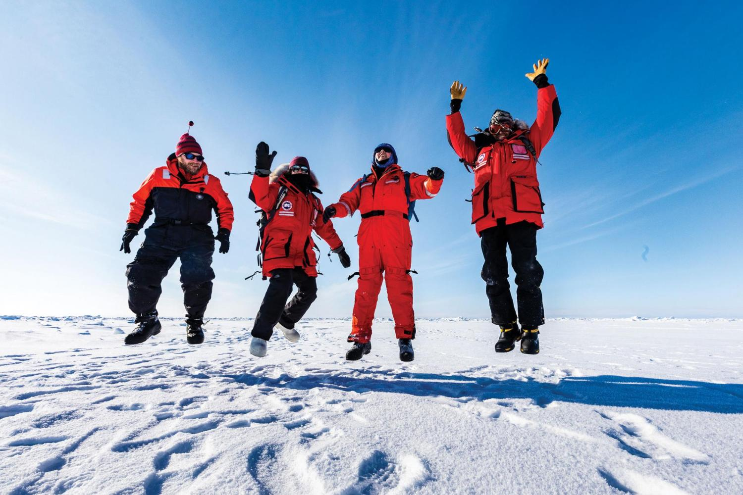CU Boulder researchers jumping in the air in the arctic