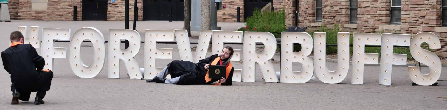 Student in front of Forever Buffs sign