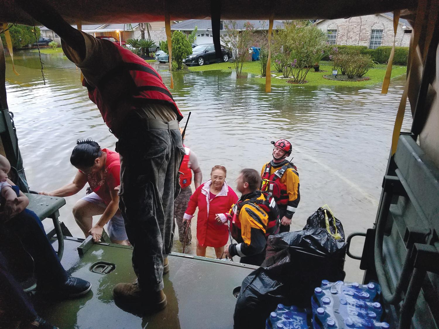Rescuers assisting individuals standing in a flooded street