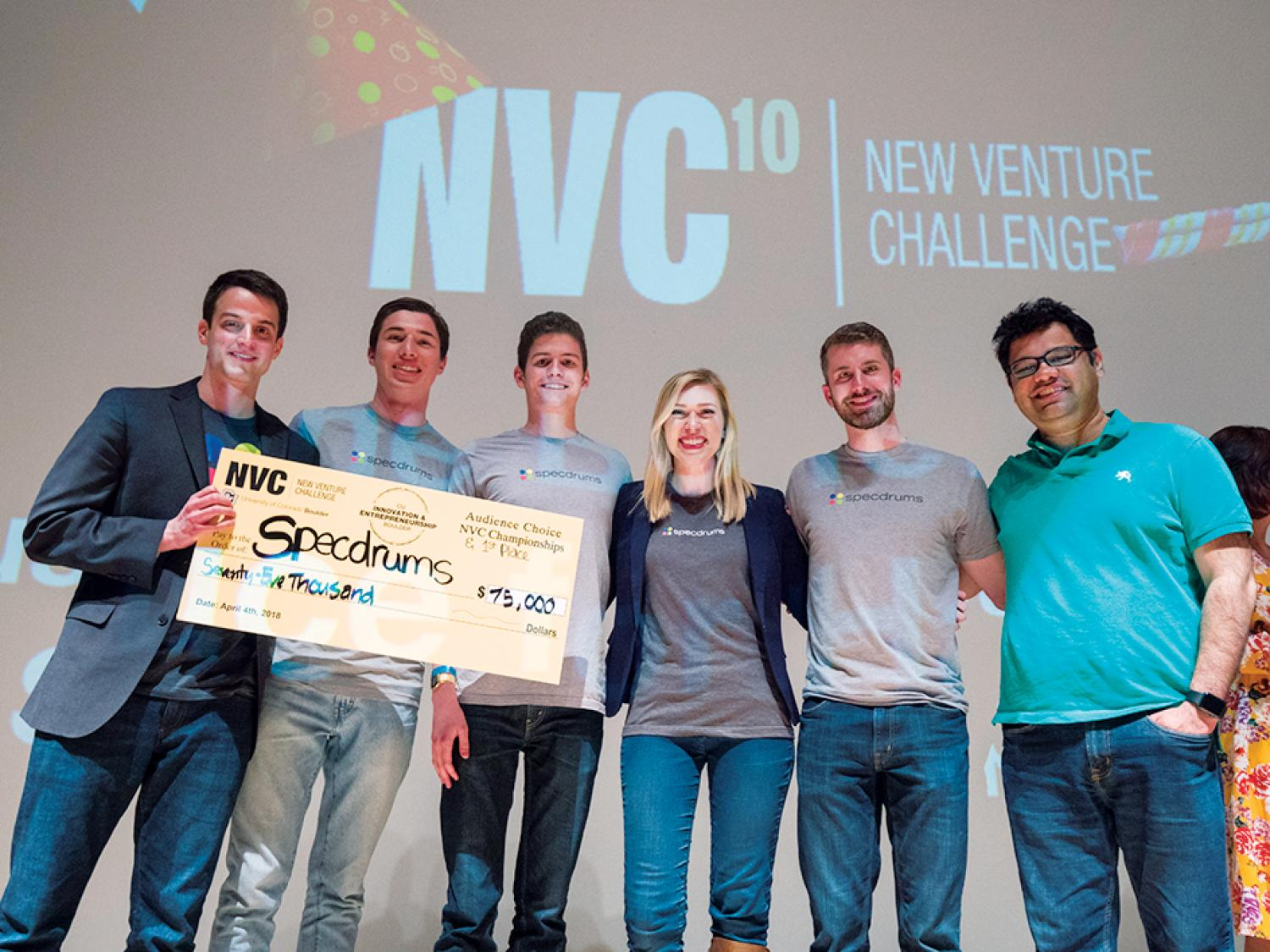 Winning team on stage with prize check