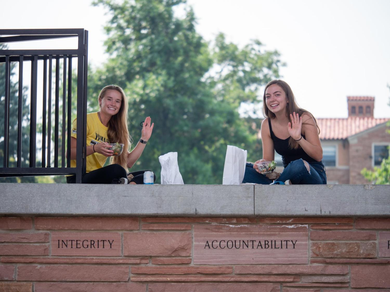 Two female students on campus eating lunch