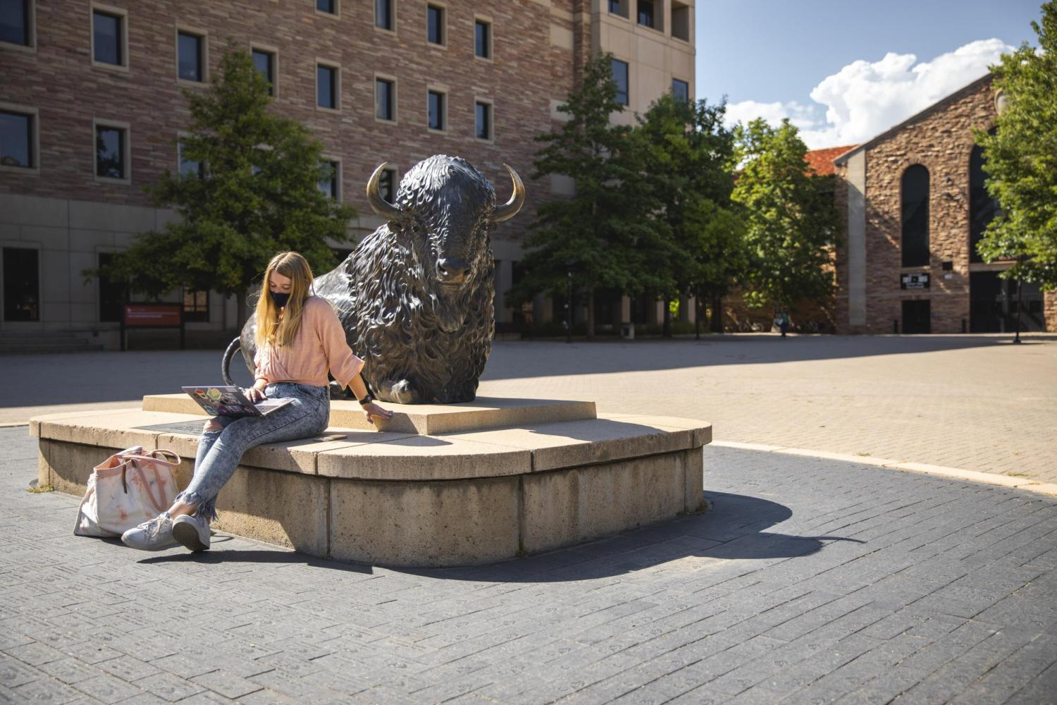 Masked female sitting by statue of Ralphie