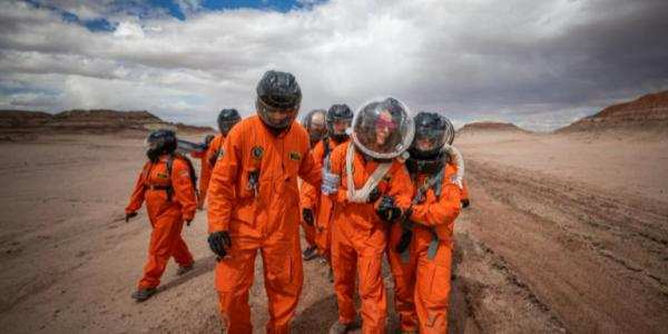 Group of students in astronaut gear walk in a simulated Martian environment