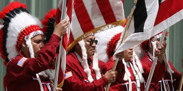 Arapaho chiefs at a gathering wearing red and white headdresses while holding flags.