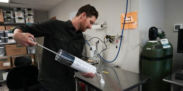 Researcher handles large syringe filled with oxygen microbubbles