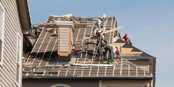 A crew builds the roof of a house.