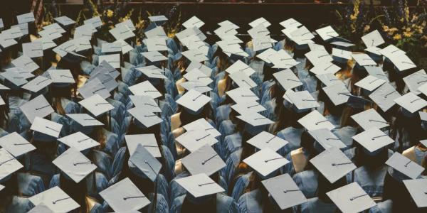 Rows of students in graduation caps and gowns
