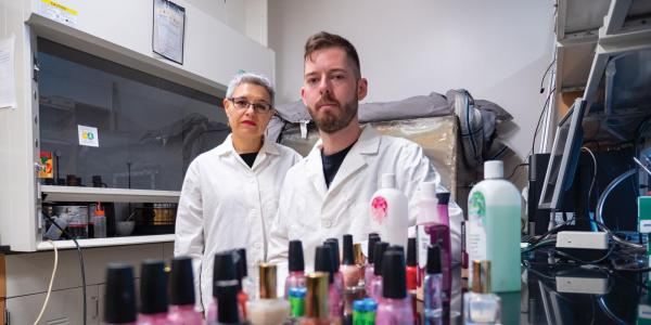 CU Boulder Professor Lupita Montoya and undergraduate student standing behind bottles of nail polish