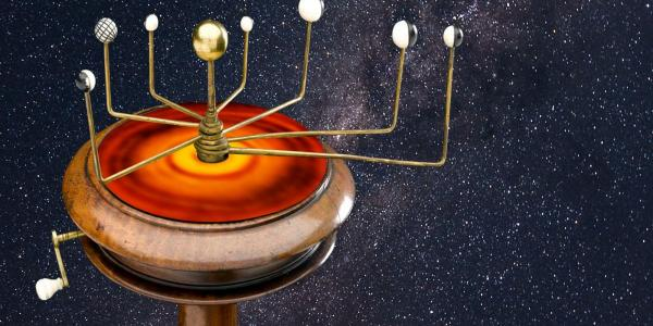 "An orrery, a type of device once used to track the movements of the planets, sitting above an infrared image of a hypothetical ""protoplanetary"" disk that may have divided the solar system early in its history."