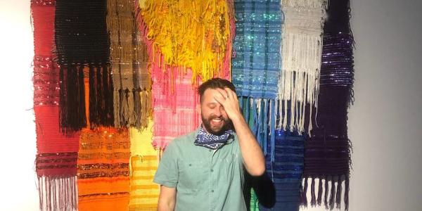 CU Boulder instructor Steven Frost smiles as he stands in front of his colorful textile artwork .