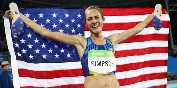 Simpson stands draped the American flag, celebrating her Olympic gold