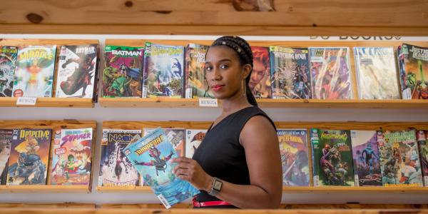 "Stephanie Toliver in a comic book store reading an issue of ""Ironheart"""