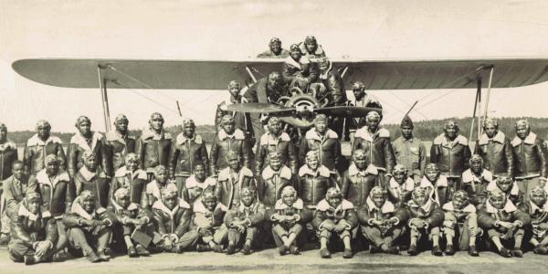 Members of a class of Tuskegee Airmen pose in front of and on an airplane.