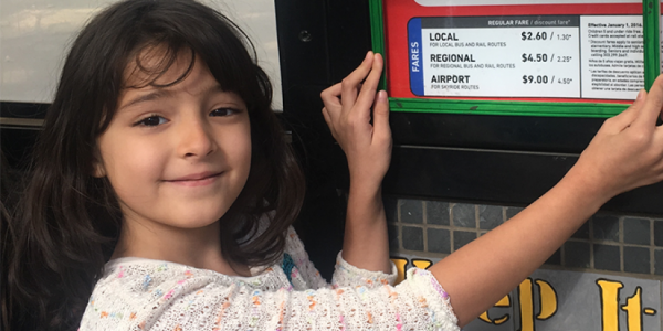 A Whittier student uses a green frame to show that she likes the sign being low enough for children to read it. Students used green and red frames to show the things they liked and didn't like about the bus stop space.
