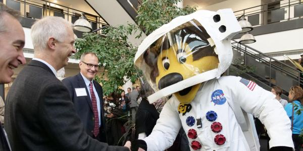 Ralphie mascot in an astronaut suit shaking hands