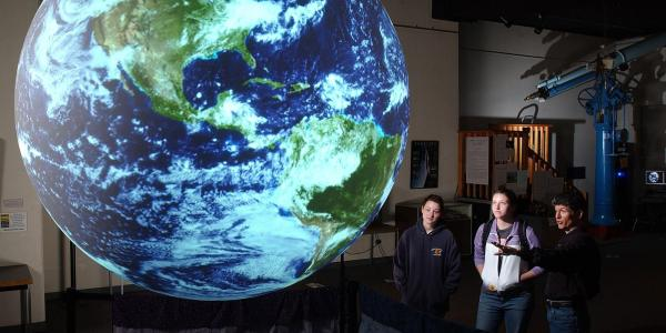 Students looking at lighted globe or Earth