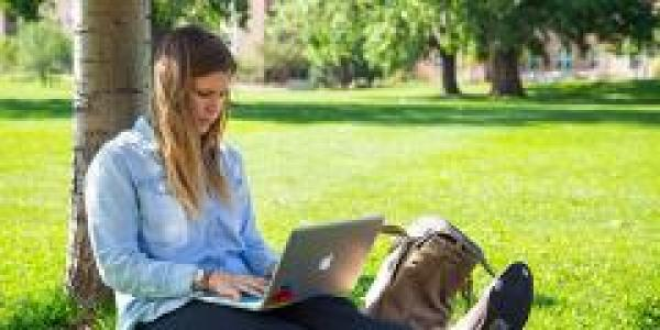 Student on laptop in park