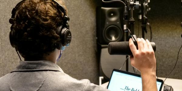 Student recording in podcast booth