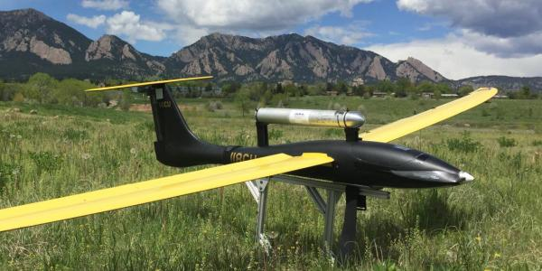 Unmanned flying vehicle parked in a field near Boulder