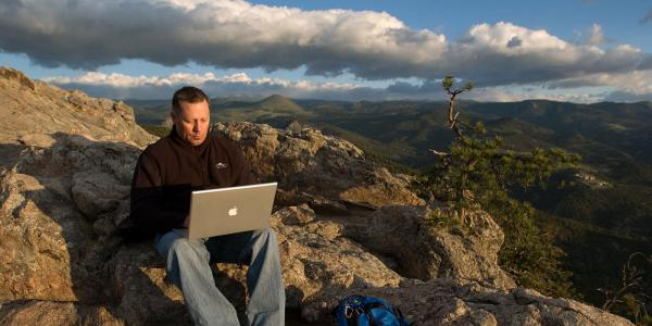 Professor on laptop in the mountains