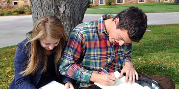 Students outside writing in notebooks