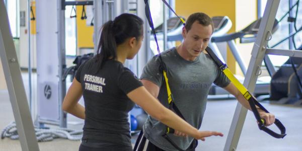 Personal trainer working with client on TRX ropes