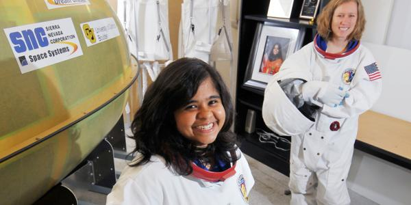 Two aerospace engineer students in astronaut suits