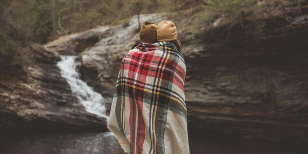 Couple under a blanket by a stream