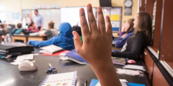 Child's hand raised in a classroom