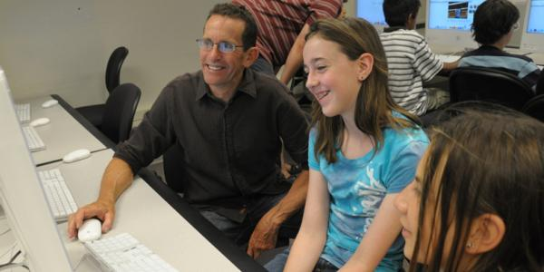Man with two young girls at a computer desk