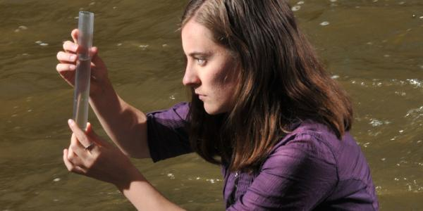 Girl looking at test tube by a creek