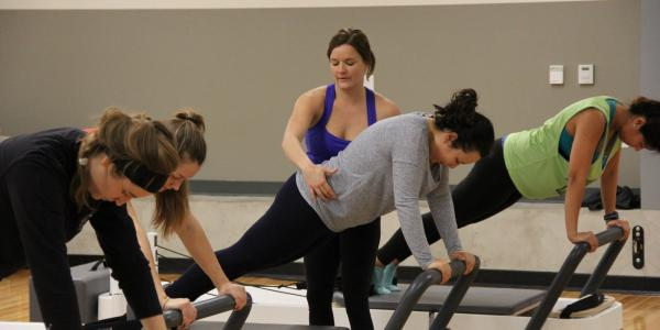 People on Pilates reformers