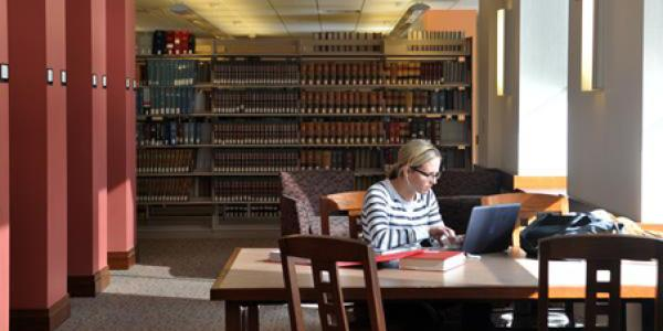 Female student studying at a table in the law library