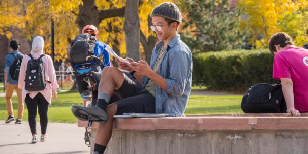 Student sitting outside on a bench