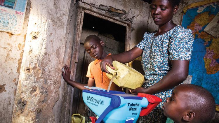 Rwandan pouring water into water filter