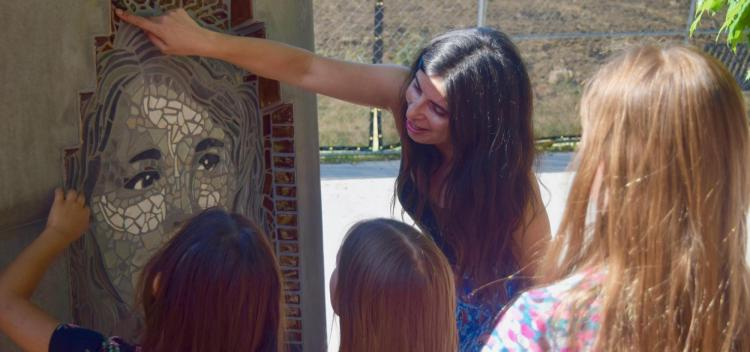 Jasmine Baetz talks to CU Science Discovery campers about one of the mosaic portraits