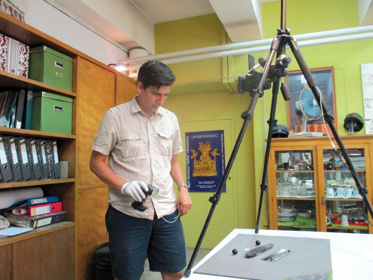 Dimitri Nakassis examining and photographing the pylos tablet