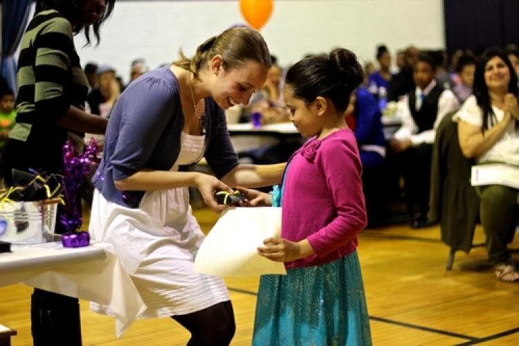 A girl receiving an award during a positive recognition campaign event in Montbello