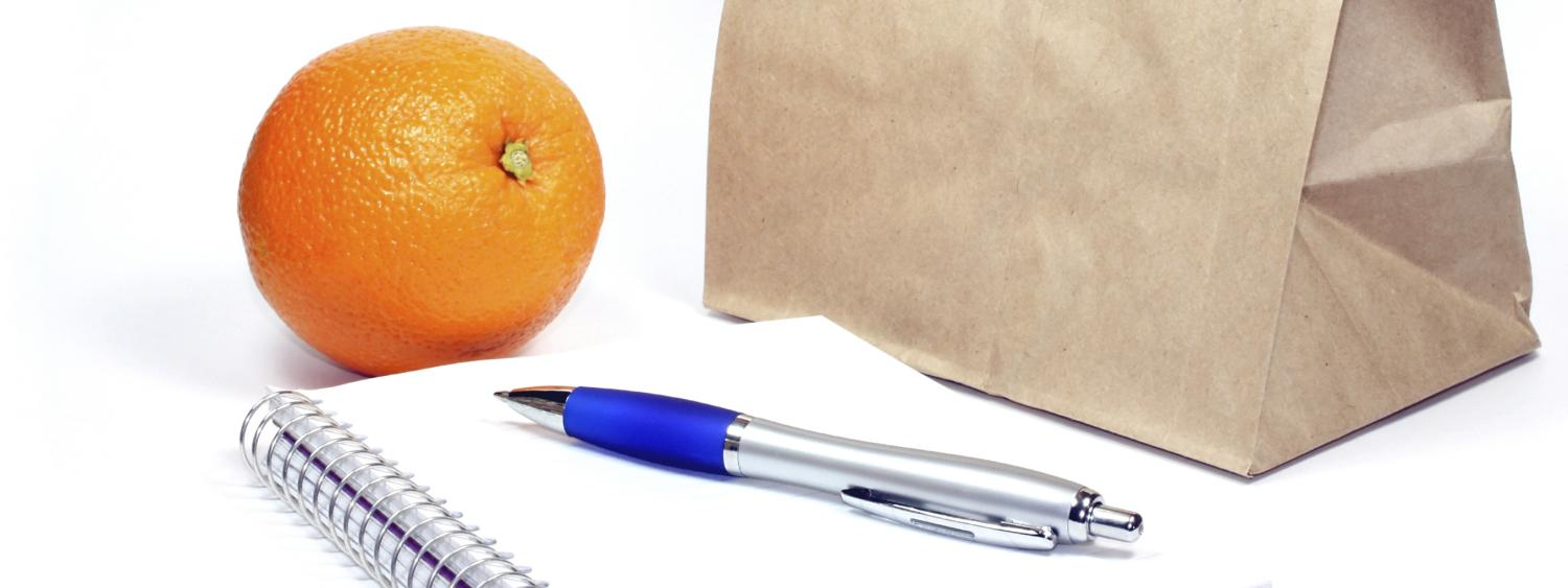 A brown lunch bag sits next to a notepad and an orange