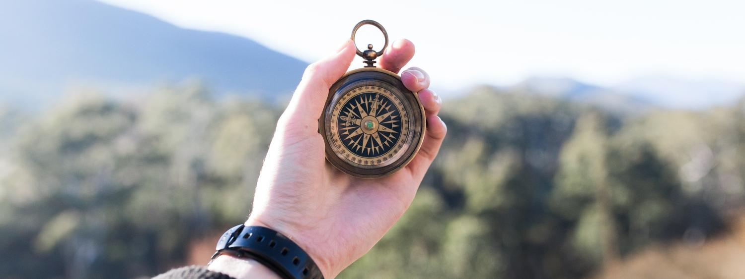 Woman holds out compass to determine direction