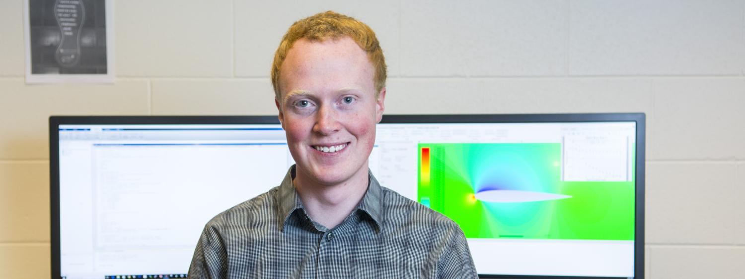 Portrait of CU student Matthew Hurst in front of monitors displaying his computer modeling graphics