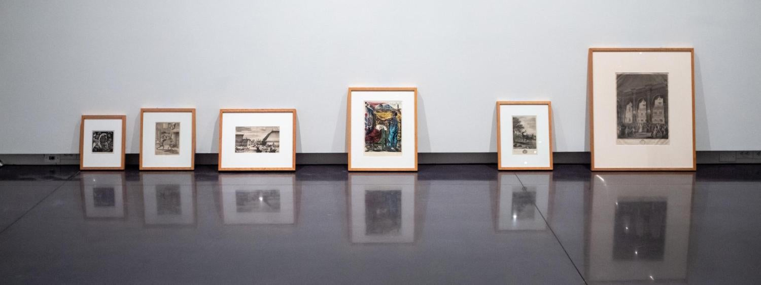 Prints sitting against a wall with reflections on the ground in the CU Art Museum.
