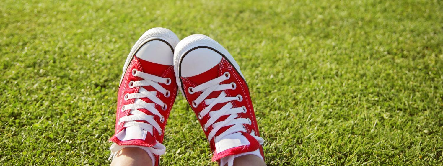 Red and white sneakers against green grass.