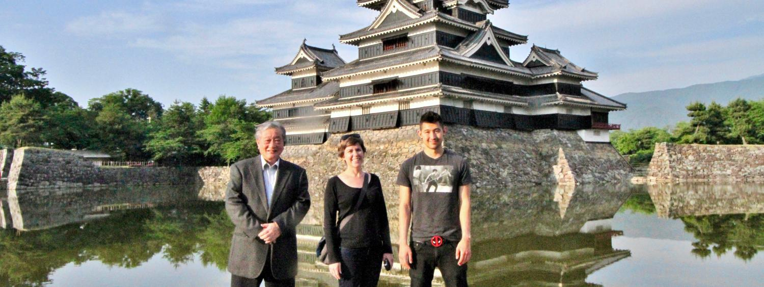Program participants pose in Japan with ancient pagoda in background