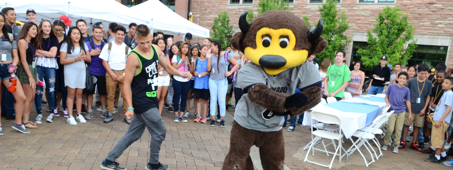 Chip dancing with a student, other students watch in background