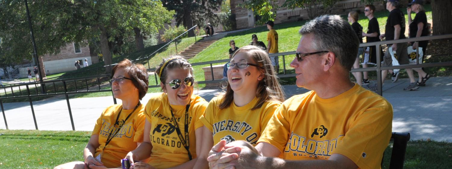 Family sits on a bench on campus during Family Weekend 2015