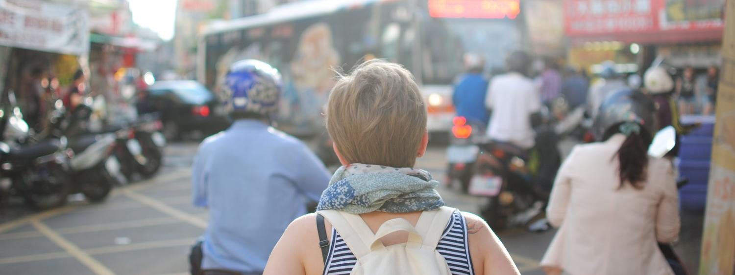 A woman wearing a backpack explores the busy streets of a city while on a study abroad trip.