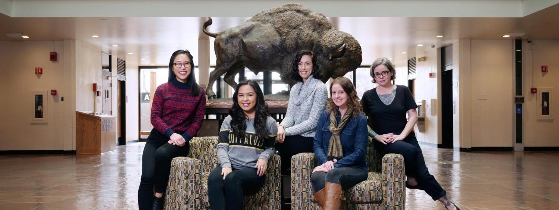 Graduate Liaison Program group sits around a buffalo statue