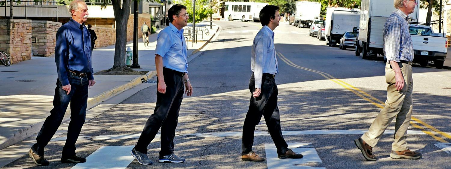 Four of the five CU Boulder Nobel laureates cross a crosswalk together
